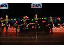 The Varsity Pom Dance Team executes a fouetté turn sequence on the IHSA State Floor.