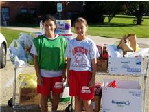 Two Eagle volleyball players help deliver the items collected from DLR's food drive.