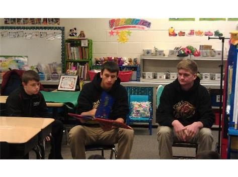 Jake Nowak, Trevor Stumpe and Tyler Myers read to first grade students at 