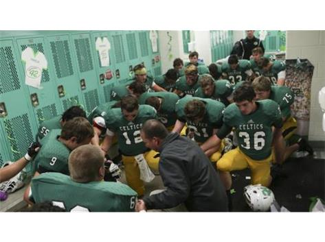 (Armando L. Sanchez / Chicago Tribune) Providence players pray in the locker room before playing Brother Rice on Friday, Oct. 17, 2014.