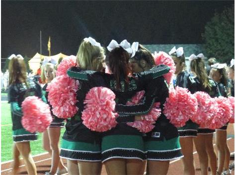 2013-14 The senior cheerleading captains huddle up to have a moment together at the close of their last Homecoming game.