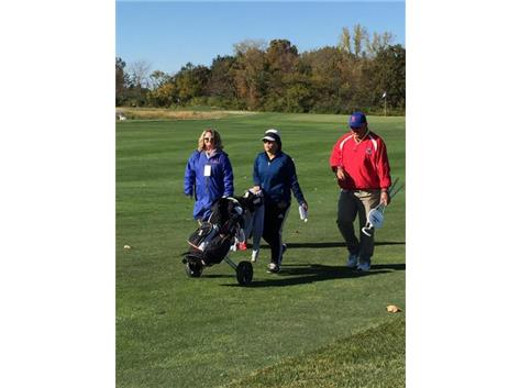 Coach Coakley and Coach Little walking with Andrea through the fairway at State