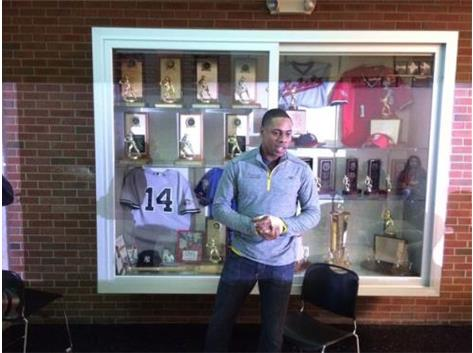 Curtis Granderson stands in front of the baseball display case that features several items from his major league career.