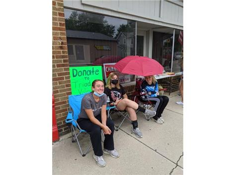 Girls dedicated to sitting in the rain to raise money for their team!