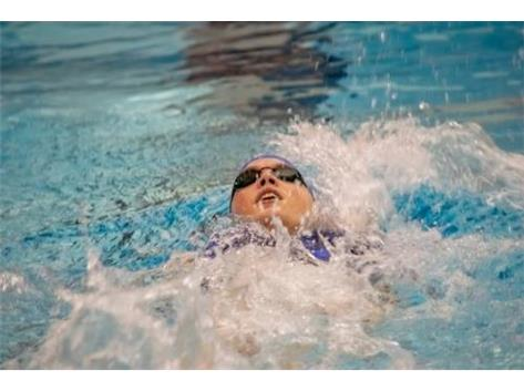 Julie swims the backstroke in her individual medley event.