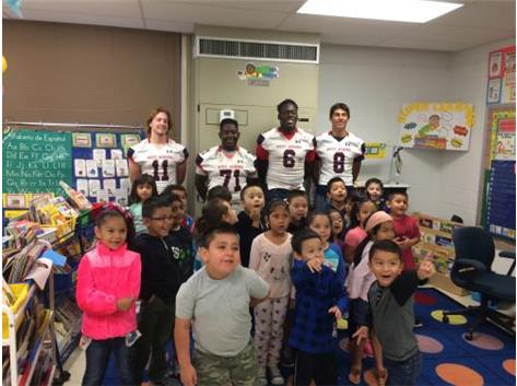 Football Players volunteer to read at Smith Elementary