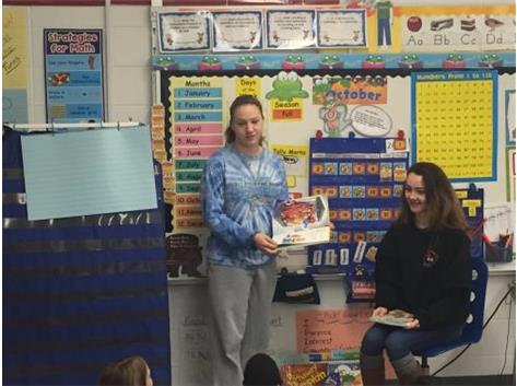 Girls Swimmers Read to Students at Schneider