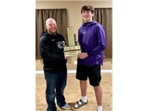 Coach Brett Miller presenting the 2019 Cory Fletcher football award to sophomore Jake Miller.