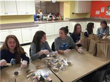 DGS Girls Soccer Seniors making over 55 brown bag lunches for PADS guests.