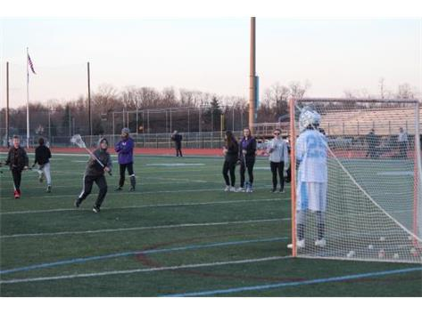 Frosh goalie, Charles Busdeker, taking shots from young players on Youth Night.