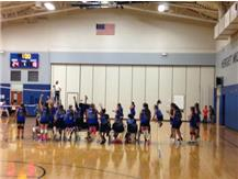 The 6th grade volleyball team celebrates after the game point.