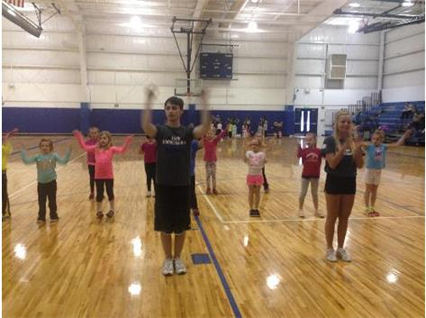 Junior Cole Huffman and Sophomore Jayden Chiaravalle teach 1st and 2nd grade campers their cheer.