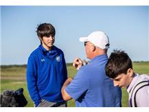 Coach Burda giving instruction to a Blue Demon golfer.