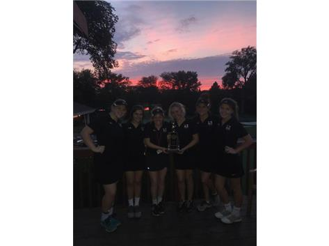 Varsity Golf posing at dusk with Caroline Griffin Tournament First Place Trophy