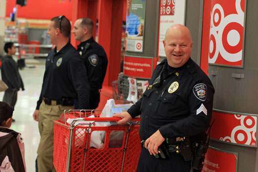 "Sgt. Rod Smith shared a laugh with fellow officers as the group checked out after shopping with local kids at Target for the annual ""Shop with a Cop"" event."