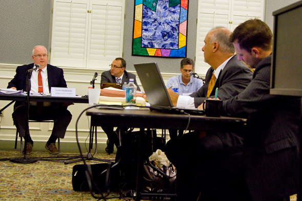 Joe Tutera (right in orange tie) listened as Councilor David Morrison explained his vote against Mission Chateau.
