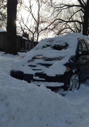 A snowed-in car reduced this Prairie Village sidestreet to a single narrow lane.