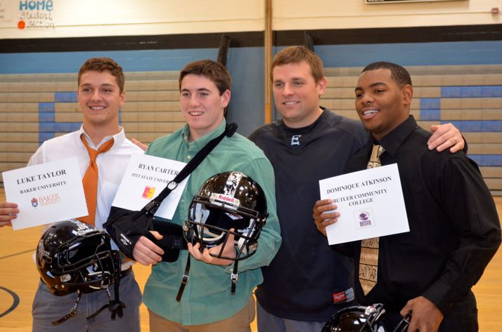 SM East football players Luke Taylor, Ryan Carter and Dominique Atkinson were congratulated by coach Dustin Delaney on their signing to plan college football.