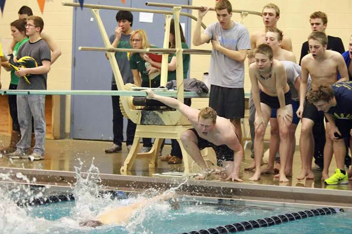 Senior Andrew McKittrick (kneeling) and other members of the SM East swim team cheered during league competition.