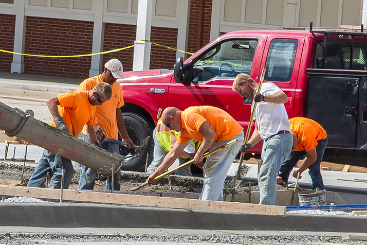 Crews poured concrete in the parking lot outside Bruce Smith Drug Store Monday.