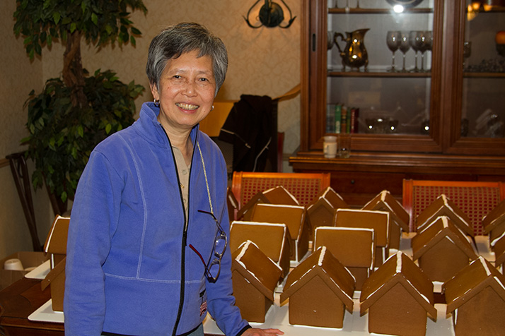 Mely Ballard bakes and assembles the gingerbread houses for the party.