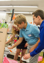 """Prairie students Maisie, Evan and Aaron made the glass shelves of a display case shine as part of their participation in """"Village People"""" in 2015. Belinder students will be working at the shops today.."""