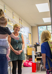First grade teacher Laura Nunnink welcomes student Lucy Roach to her new classroom.