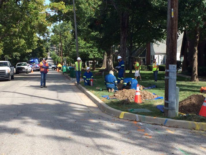 Kansas Gas crews in blue fire retardant suits work on repairing the damaged line.