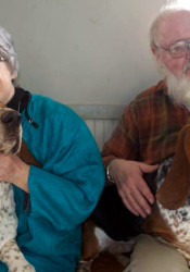 Missy and Doug Taylor at home with two of the four Basset Hounds they now own.