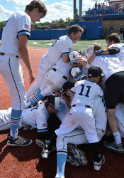 The Lancers form a mosh pit near first base after beating Lawrence Free State in extra innings. Photo by Joseph Cline