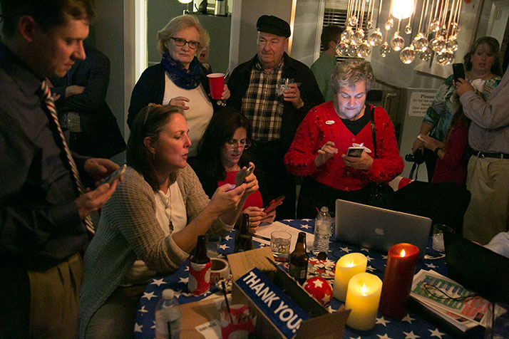 Melissa Rooker, center in glasses, checked early results Tuesday with supporters.