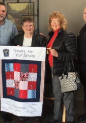 (From left) Merriam Police Chief Mike Daniels accepts prayer quilt from Janis Grace and Donna Enloe with Capt. Todd Allen.