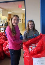 Savannah Bittner (left) and Matia Ianni, both eighth graders, load a Red Bag stuffed with gifts.