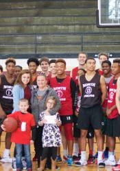 The Shawnee Mission North basketball team poses for a picture with a few Macan family members after they surprises the Macans with a little Christmas gift.