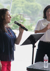 Kristy Lambert sang the National Anthem as the rains fell around Harmon Park Pavilion Tuesday morning.
