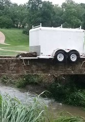 Flash flooding washed trailer belonging to Boy Scout Troop 192 at Old Mission United Methodist from the church parking lot and onto a golf cart bridge at Kansas City Country Club. Photo by Jim Poplinger.