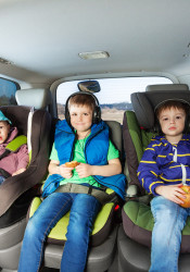 Three happy boys, age-diverse brothers, sitting in safety car seats, snaking and listening the music during car trip