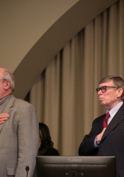 Hannes Zacharias, left, says the pledge of allegiance ahead of a Board of County Commissioners meeting.