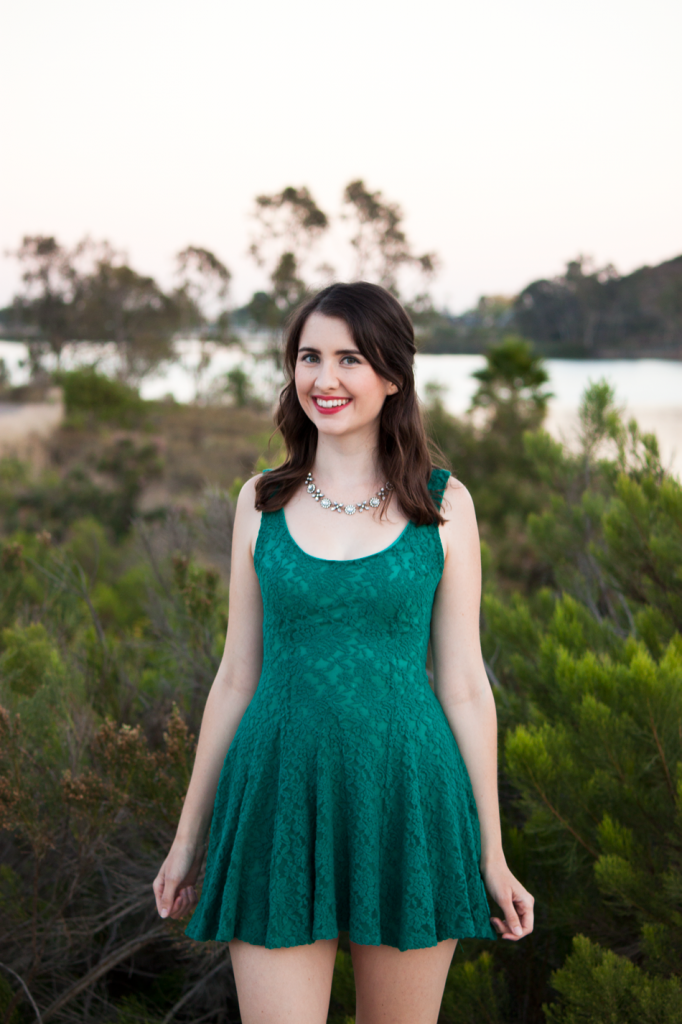 Green lace skater dress with red lipstick and a sparkly necklace