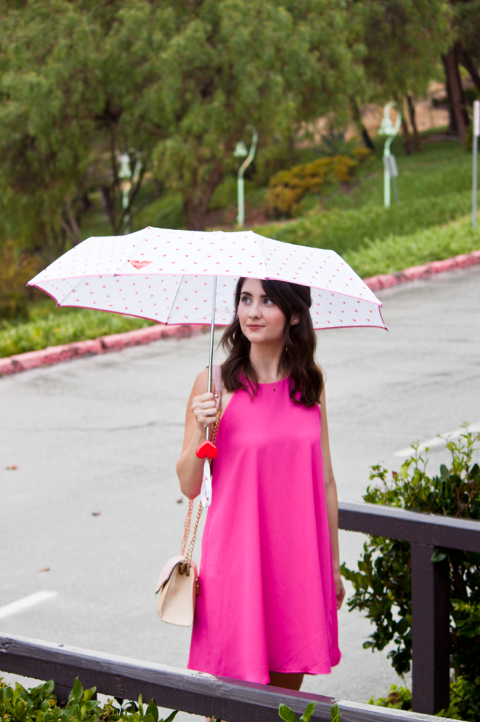 Pink swing dress with a pastel colorblock vegan leather bag and a heart print umbrella