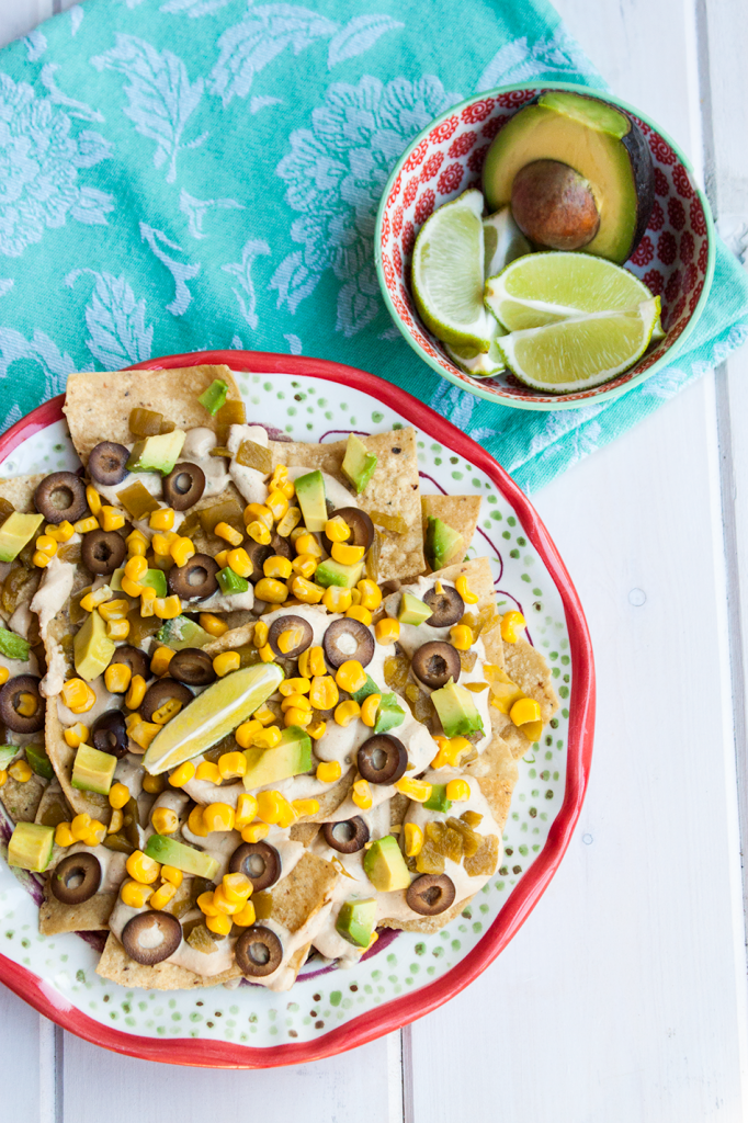 Southwestern vegan Nacho Recipe loaded with corn, chile, avocado and olives plus a vegan cheese sauce.