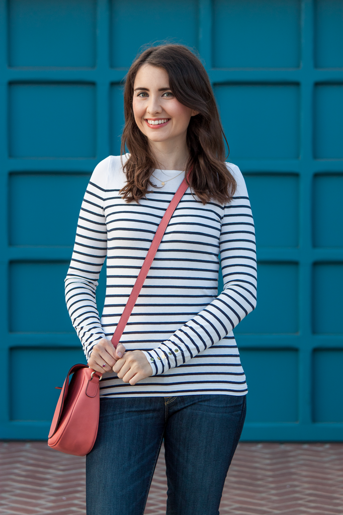 Pink vegan crossbody bag with a striped top and jeans