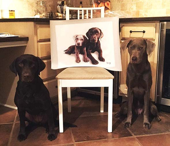 2 cute dogs standing near their oil portrait
