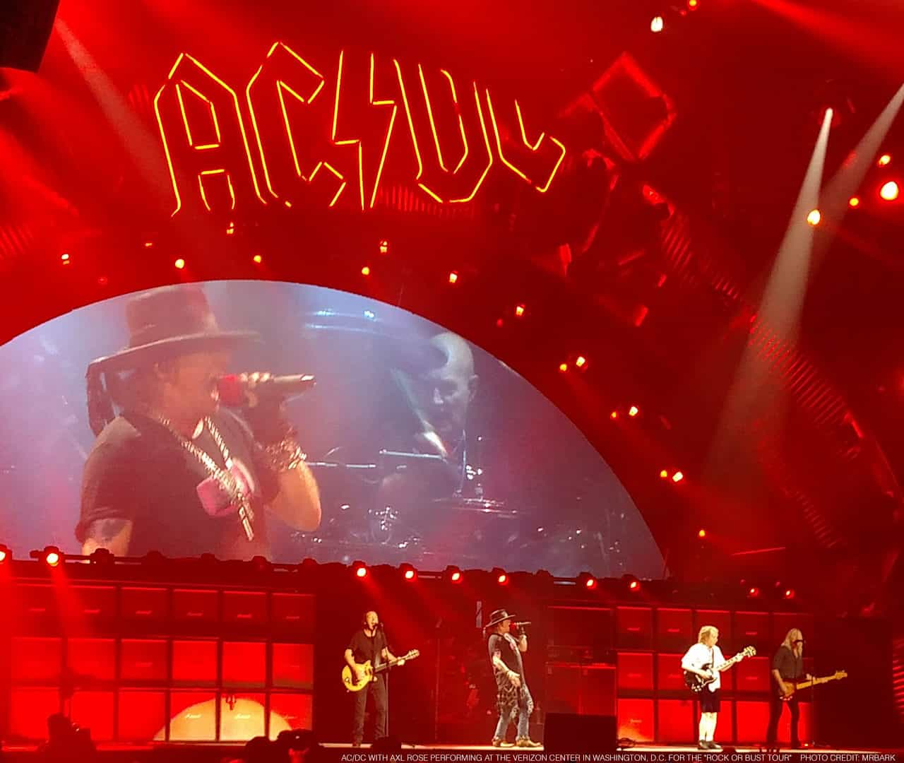 "AC/DC with Axl Rose performing at the Verizon Center in Washington, D.C. for the ""Rock or Bust Tour"" on September 17, 2016. On stage from left to right: Stevie Young, Axl Rose, (obscured behind Axl but visible on the monitor, Chris Slade), Angus Young, and Cliff Williams"