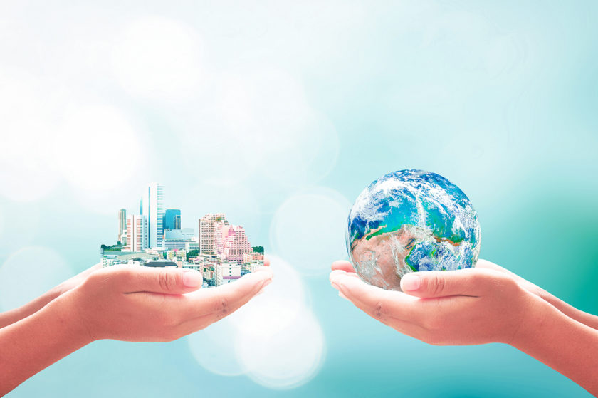 Hands holding city and globe symbolizing corporate social responsibility