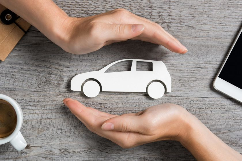 hands around a car symbolizing auto repair insurance or extended car warranty
