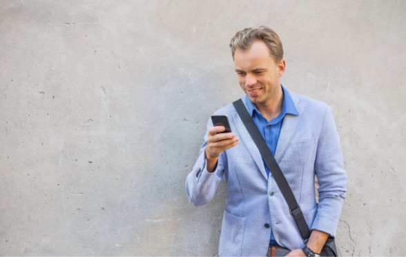 Man Leaning Against Wall Looking at Phone