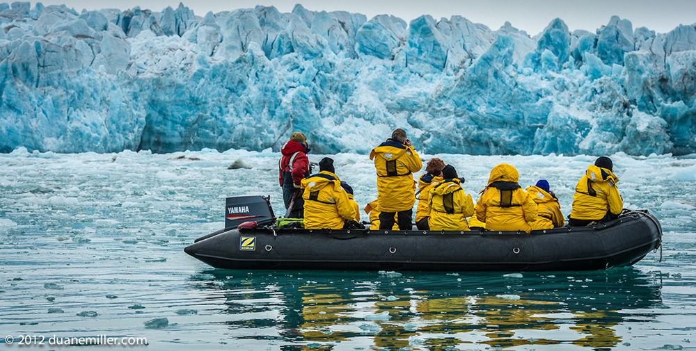 Arctic expedition passengers drift by a spectacular glacial ice formation by Zodiac cruiser. Photo: Duane Miller