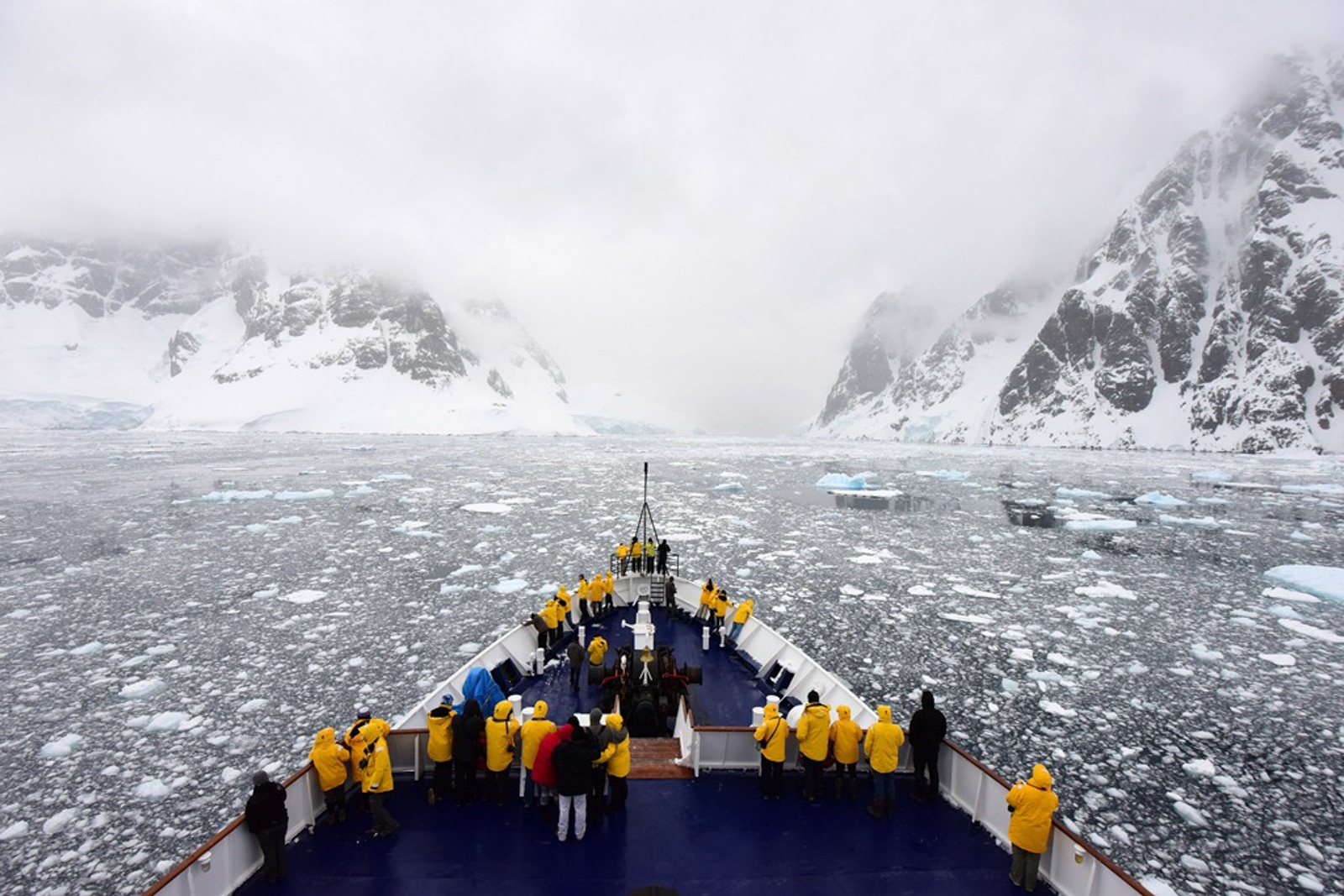 Passengers gather on deck to appreciate the icy waters of the Lemaire Channel on an Antarctic expedition.