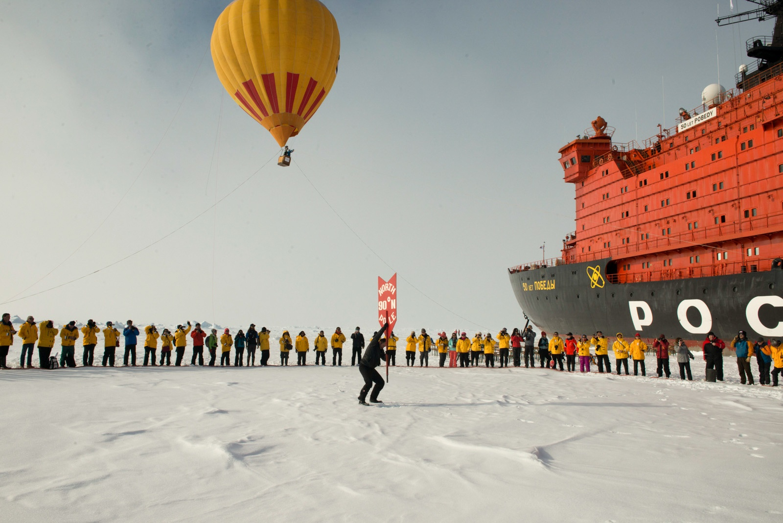 Passengers celebrate reaching the North Pole in a gathering on the thick, multi-year Arctic sea ice.